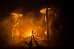 för objekttid för bakgrund begrepp isolerad white Kontur av ett mananseende mellan timglas med rök och ljus på en mörk bakgrund Royaltyfria Bilder