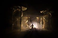 för objekttid för bakgrund begrepp isolerad white Kontur av ett mananseende mellan timglas med rök och ljus på en mörk bakgrund Arkivfoto