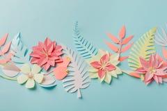 För origamifower för pappers- hantverk idé för garnering idérik tropiska blommor och sidor på blå pastellfärgad bakgrund, sommart royaltyfri bild