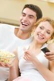 för par hålla ögonen på för tv tillsammans Arkivfoto