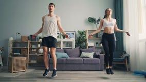 För parbanhoppning för ung man och kvinnarep i huset som tillsammans inomhus gör sportar arkivfilmer