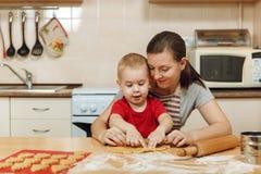 För pojkehjälp för liten unge moder som lagar mat det ljust rödbrun kexet Lycklig familjmamma och barn i helgmorgon hemma förhåll arkivfoton