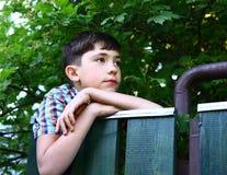 För pojkeklättring för Preteen stiligt staket för by royaltyfri fotografi