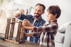 För pojkeportion för fader och för liten son hemmastatt stående spikar bulta för farsa in i glat samarbete för stol fotografering för bildbyråer