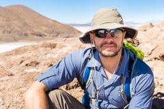 För portrainsammanträde för man turist- berg Salar De Uyuni Bolivia Royaltyfri Foto