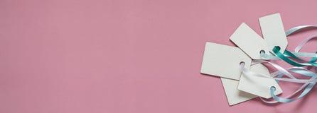 För prisförsäljning för tomt papper etiketter på rosa bakgrund Trevliga delikata pastellfärgade färger Royaltyfri Foto