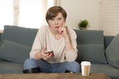 För röd borrad och lynnig användande internet app hårkvinna för ung attraktiv 30-tal som förargas på mobiltelefonen som sitter de arkivfoto