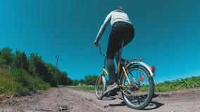 För ridningtappning för ung kvinna cykel längs en lantlig väg i en by arkivfilmer