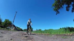 För ridningtappning för ung kvinna cykel längs en lantlig väg i en by lager videofilmer