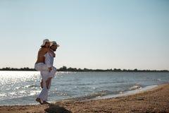 för ridtur på axlarnaritt för par lycklig kust för hav Fotografering för Bildbyråer