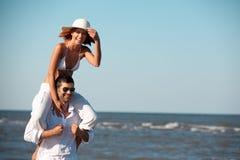 för ridtur på axlarnaritt för par lycklig kust för hav Royaltyfri Bild