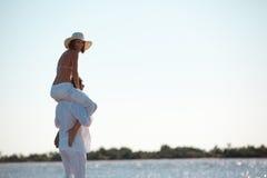 för ridtur på axlarnaritt för par lycklig kust för hav Arkivfoton
