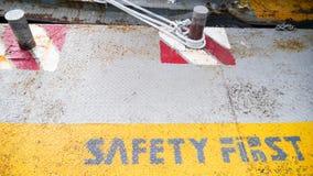 För säkerhet för gulingetikett först symbol för tecken för golv på grå färgmetalltextur Royaltyfria Foton