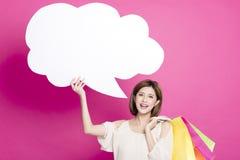 För för shoppingpåsar och visning för kvinna hållande dialog fotografering för bildbyråer