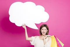 För för shoppingpåsar och visning för kvinna hållande dialog arkivbilder