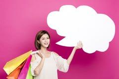 För för shoppingpåsar och visning för kvinna hållande dialog arkivfoton