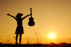 för silhouettesolnedgång för gitarr lycklig kvinna Arkivfoto