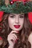 För skönhetflicka för jul som eller för nytt år stående isoleras på röd bakgrund Härlig kvinna med den lyxiga makeup- och julkran Arkivfoto