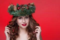 För skönhetflicka för jul som eller för nytt år stående isoleras på röd bakgrund Härlig kvinna med den lyxiga makeup- och julkran Arkivbild