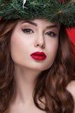 För skönhetflicka för jul som eller för nytt år stående isoleras på röd bakgrund Härlig kvinna med den lyxiga makeup- och julkran Arkivbilder