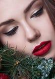För skönhetflicka för jul som eller för nytt år stående isoleras på röd bakgrund Härlig kvinna med den lyxiga makeup- och julkran Arkivfoton