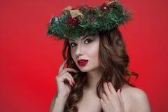 För skönhetflicka för jul som eller för nytt år stående isoleras på röd bakgrund Härlig kvinna med den lyxiga makeup- och julkran Royaltyfri Bild
