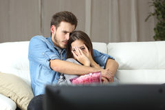 För skräcktv för par hållande ögonen på film hemma Arkivfoto