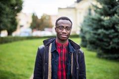 För skuldraläder för modern högskolestudent bärande påse, ett afrikansk amerikangrabbanseende vid väggen på gatan arkivfoto