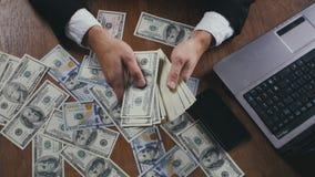 För slut händer upp av en affärsman som i regeringsställning räknar pengarsammanträde på tabellen Begrepp av lönen eller vinst arkivfilmer