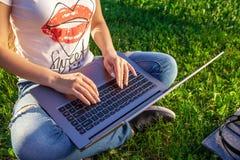 För slut händer upp på tangentbordet Kvinnan som arbetar på bärbar datorPCdatoren parkerar in, på solskengräsmatta för grönt gräs royaltyfria foton