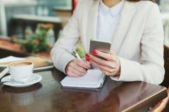 För smartphone- och handstilanmärkningar för affärskvinna hållande closeup utomhus Royaltyfri Bild