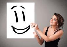 För smileyframsida för ung kvinna hållande teckning Royaltyfria Bilder