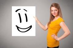 För smileyframsida för ung kvinna hållande teckning Arkivbilder