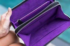 För snakeskinpytonormen för mode räcker den lyxiga plånboken i kvinna sammanträde nära simbassängen, Bali arkivfoton