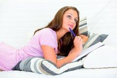 för sofakvinna för anteckningsbok eftertänksam nätt writing Arkivbilder