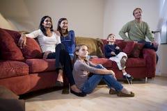 för sofatv för familj interracial sittande hålla ögonen på Royaltyfri Fotografi
