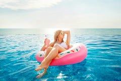 för sommarterritorium för katya krasnodar semester Kvinna i bikini på den uppblåsbara munkmadrassen i SPA simbassängen royaltyfria foton