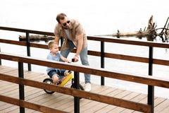 för sonridning för fader undervisande cykel på bron arkivbild