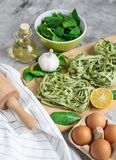 För spenatpasta för förberedelse som italiensk rå hemlagad grön tagliatelle lagar mat baka köksbordet royaltyfri fotografi