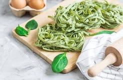 För spenatpasta för förberedelse som italiensk rå hemlagad grön tagliatelle lagar mat baka köksbordet arkivfoto