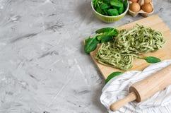 För spenatpasta för förberedelse som italiensk rå hemlagad grön tagliatelle lagar mat baka köksbordet royaltyfri bild