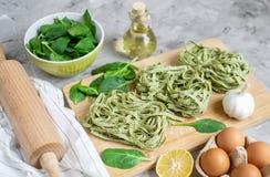 För spenatpasta för förberedelse som italiensk rå hemlagad grön tagliatelle lagar mat baka köksbordet arkivbild