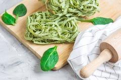För spenatpasta för förberedelse som italiensk rå hemlagad grön tagliatelle lagar mat baka olika ingredienser för köksbord royaltyfri foto