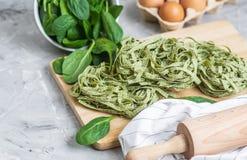 För spenatpasta för förberedelse som italiensk rå hemlagad grön tagliatelle lagar mat baka olika ingredienser för köksbord arkivfoton