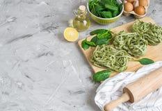 För spenatpasta för förberedelse som italiensk rå hemlagad grön tagliatelle lagar mat baka olika ingredienser för köksbord arkivbild