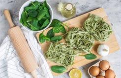 För spenatpasta för förberedelse som italiensk rå hemlagad grön tagliatelle lagar mat baka olika ingredienser för köksbord arkivfoto
