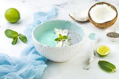 För spirulinasmoothie för strikt vegetarian som blå bunke och chiapuddingöverträffas med kokosnötflinga- och limefruktpiff arkivbild