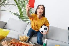 För sportfan för ung kvinna hållande ögonen på match i gul t-skjorta ett rött kort royaltyfri bild