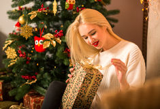 För ståendehållen för den unga kvinnan gåvan i jul färgar stil fotografering för bildbyråer