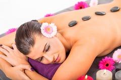 För stenmassage för ung attraktiv kvinna varm wellness royaltyfria foton